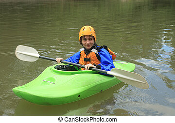 Teenager Kayaking - A teenager wearing a helmet and safety...