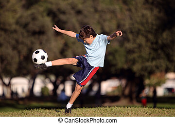 Young boy with soccer ball in park - Young boy kicking a...