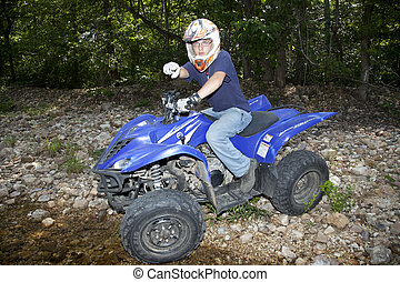 ATV Riding - A teenager riding an ATV by a river.