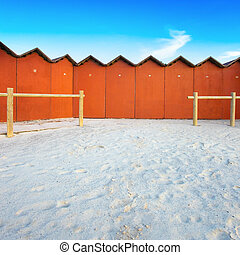 Red bathing huts on a white beach