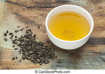 gunpowder green tea - a white cup of drink and loose leaves...