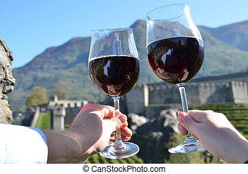 Pair of wineglasses in the hands. Bellinzona, Switzerland