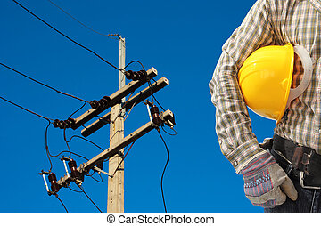 Electrician worker at work against electric post and blue...