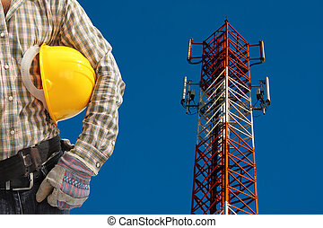 technician against telecommunication tower, painted white...