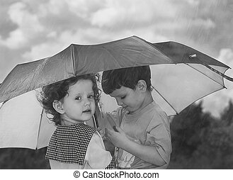 little girl and boy hiding under an umbrella from the rain,...