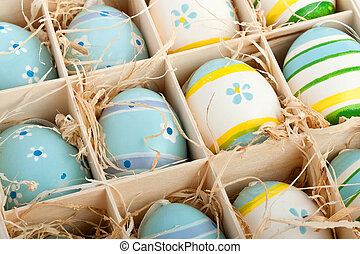 assorted colorful painted easter eggs in a wodden box -...