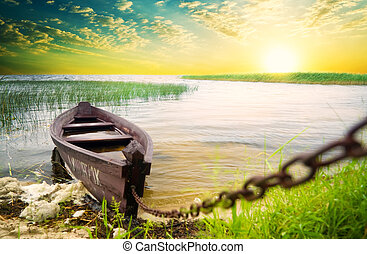 Boat at coast against sunset. Nature composition.