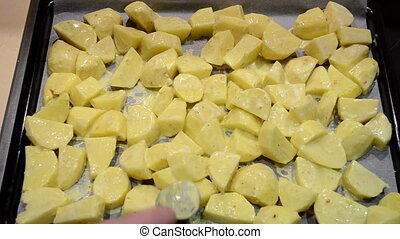 spiced potatoes bake pan - hands put spiced sliced potatoes...
