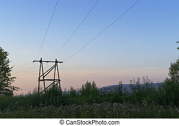 Overhead power line with a wooden pylons on sunset sky...