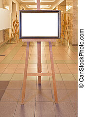 brown wood picture frame on easel in art gallery hall