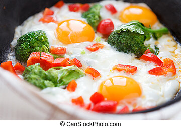 Fried eggs in a frying pan with broccoli and peppers,...