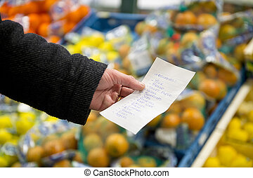 Shopping list with groceries - Hand, holding a shopping list...