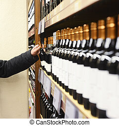 Man Choosing Wine Bottle From Shelves In Store - Caucasian...