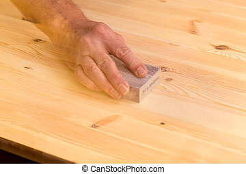 Mans hand on sanding block on pine wood - Man rubbing...