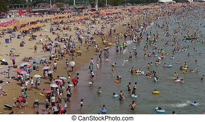 A lot of people at crowded bathing sandy beachPeople swim in...