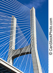 Modern bridge fragment: white cables against bright blue sky