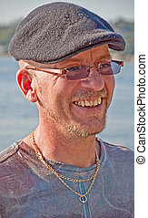 Middle Age Man Smiling with Cap On Outdoors - This middle...