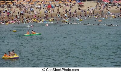 A lot of people at crowded bathing sandy beach.Boat & People swim in sea