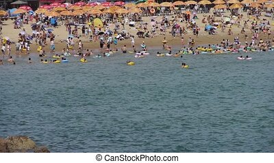 A lot of people at crowded bathing sandy beach.People swim...