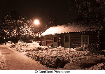 Log cabin - A log cabin at night covered in snow along a...