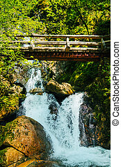Wooden bridge over waterfalls in the mountains