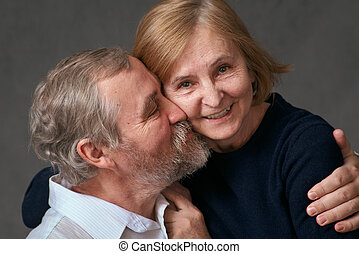 Happy elderly couple - An elderly man hugs and kisses his...