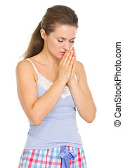 Young woman in pajamas praying before sleep