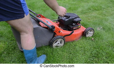 worker push grass mower - man gardener worker in shorts and...
