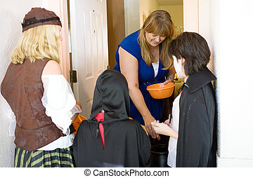 Greeting the Trick or Treaters - Friendly homeowner passing...