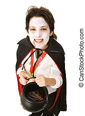 Halloween Vampire with Candy - Cute adolescent boy dressed...