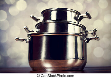 Steel cooking pots with bokeh at background