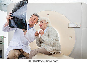 Doctor And Patient Looking At CT Scan X-ray - Mature male...