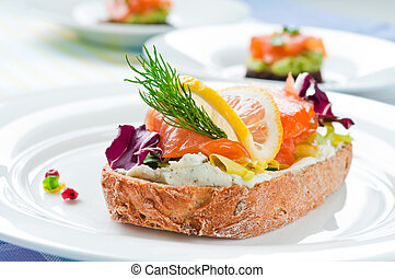 Sandwich with smoked salmon, soft cheese and vegetables
