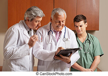 Senior Male Doctor With Colleagues - Happy senior male...