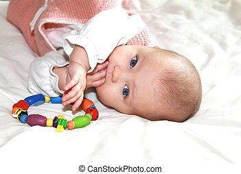 Beautiful baby girl sucking the fingers and holding the...