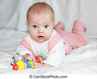 Surprised beautiful baby girl playing with colorful toy