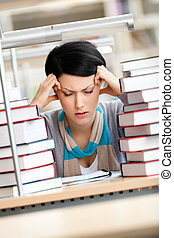 Tired young woman surrounded with books