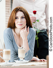 Woman at the coffee house and man with rose behind her