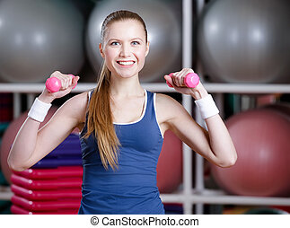 Beautiful athlete woman working out with dumbbells