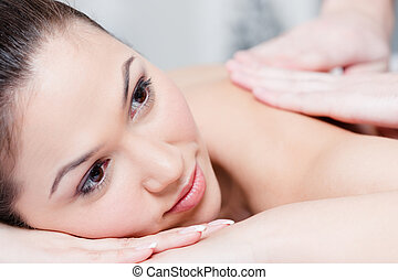 Beautiful woman relaxing in massage salon