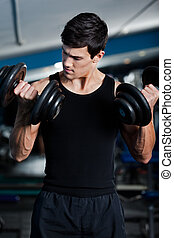 Handsome muscular man uses his dumbbells to exercise flexing...