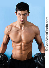 Handsome muscular man uses the dumbbell - Handsome muscular...