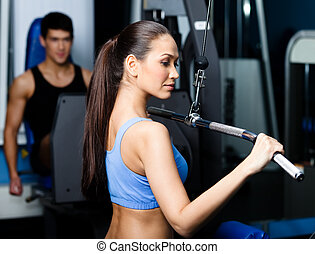 Athletic young woman works out on fitness gym equipment -...