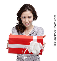 Young woman reaches out a gift wrapped in red paper,...