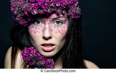 Close up of blue-eyed girl with flowers - Close-up portrait...