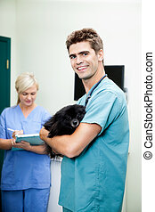 Veterinarian Doctor Carrying A Dog With Female Nurse Writing On