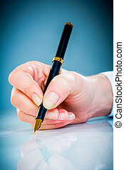 Woman's hand and pen - Woman's hand with a pen on a blue...
