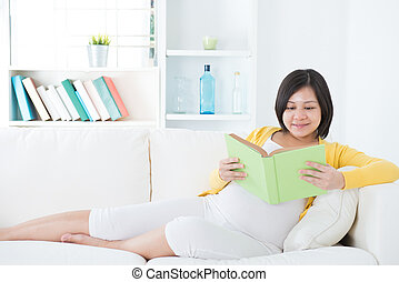 Asian pregnant woman reading a book on sofa
