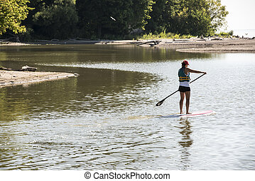 Woman on surf board with paddle. - A woman on a surf board...