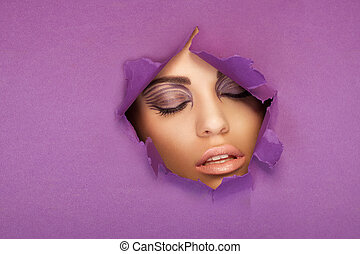 Beautiful woman with closed eyes looking through a torn hole...